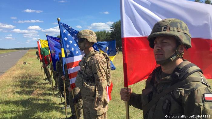 Soldiers representing NATO nationals with flags during opening ceremonies for exercise Anakonda June 6, 2016 in Oleszno, Poland