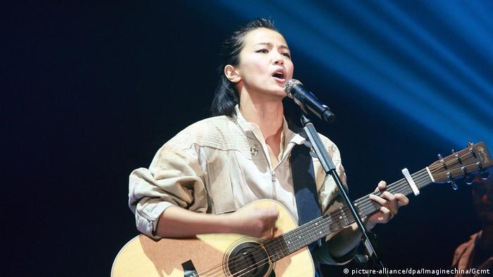 Sängerin Denise Ho Wan-see, mit Gitarre, singt in ein Mikrofon