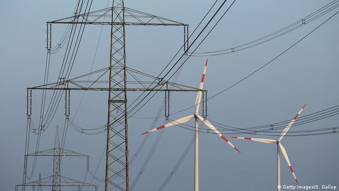 Wind turbines visible behind power lines in Germany (Photo: Getty Images/S. Gallup)