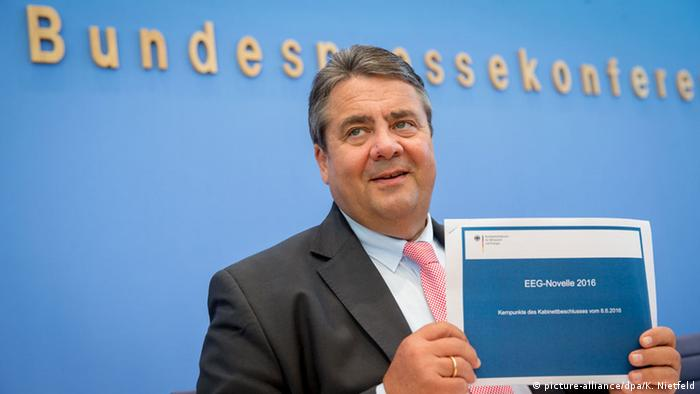 German Vice-Chancellor Sigmar Gabriel holding a booklet of agreed-upon renewable energy law reforms (Photo: picture-alliance/dpa/K. Nietfeld)