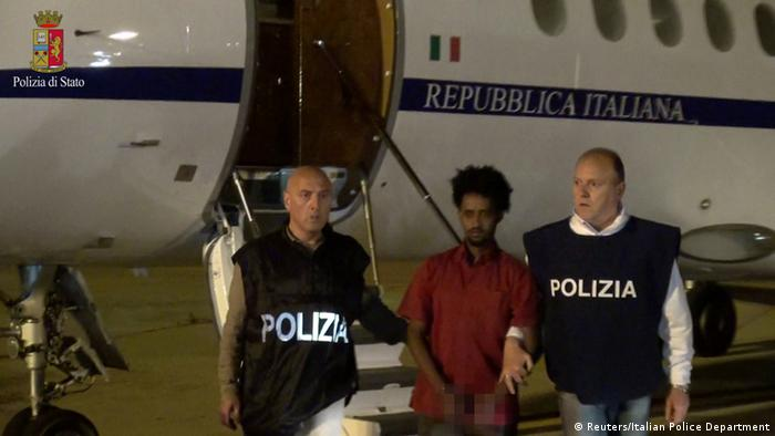 Medhanie Yehdego Mered (C), 35, is pictured with Italian policemen as they land at Palermo airport, Italy, following his arrest in Khartoum, Sudan, on May 24 (Photo: Reuters/Italian Police Department)