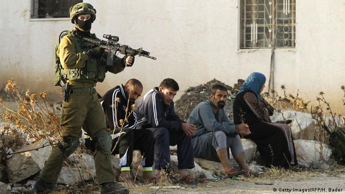 An Israeli soldier keeps watch as Palestinians sit nearby after the army entered the village of Yatta in the occupied West Bank on June 9, 2016 in search for clues leading to an attack the previous night in the Israeli city of Tel Aviv ins which four people were killed and 16 others wounded (Photo: +++ (C) Getty Images/AFP/H. Bader)