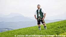 A Bavarian man in lederhosen stands on a mountain (picture-alliance/Bildagentur-online/M. Gann-Yay)
