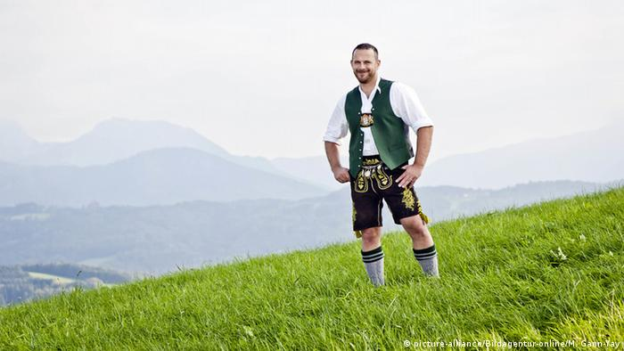 A Bavarian in lederhosen stands on an alpine mountaintop (picture-alliance/Bildagentur-online/M. Gann-Yay)