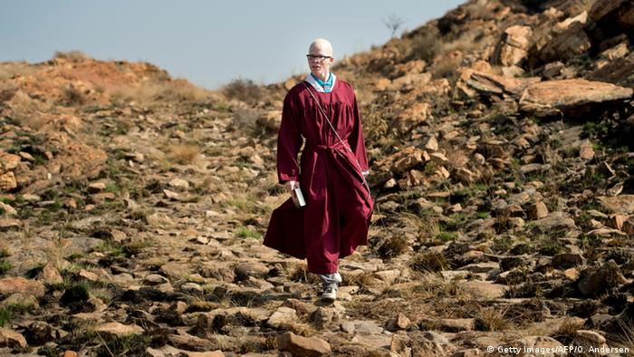 An albino man wearing a red robe walks alone in countryside near to Johannesburg, South Africa.