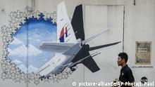 FILE - In this Tuesday, Feb. 23, 2016, file photo, a waiter walks past a mural of flight MH370 in Shah Alam outside Kuala Lumpur, Malaysia. Malaysia's government said Thursday, May 12, 2016, that two more pieces of debris, discovered in South Africa and Rodrigues Island off Mauritius, were almost certainly from Flight 370, which mysteriously disappeared more than two years ago with 239 people on board. +++ (C) picture-alliance/AP Photo/J. Paul