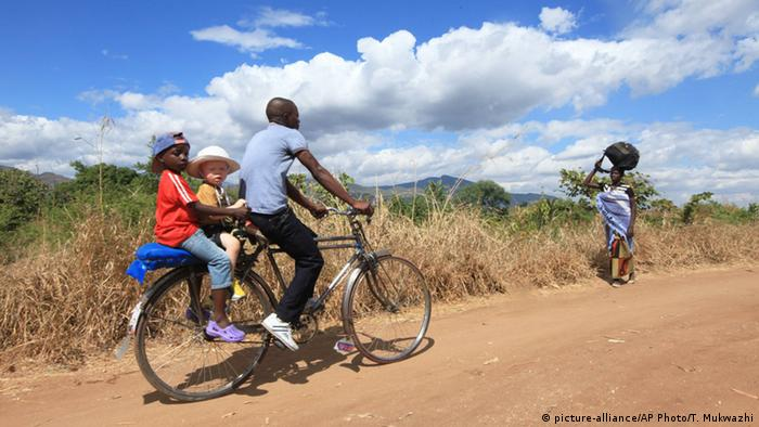 Razik Jaffalie from Malawi with rides his bike with his two sons on the back, including Cassim, who has albinism. (Photo: AP)