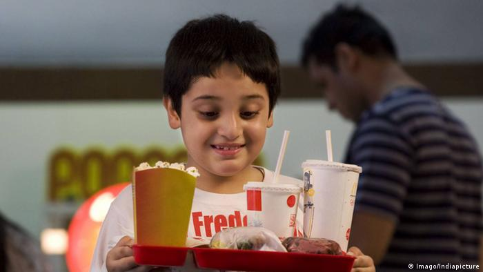 Child with greasy food and a soft drink (Imago/Indiapicture)