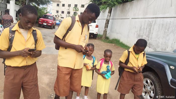 Children walking from school with mobile phones