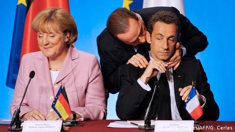 Silvio Berlusconi umarmt Nicolas Sarkozy neben Angela Merkel