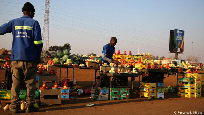 Black men sell vegetables at the side of the road