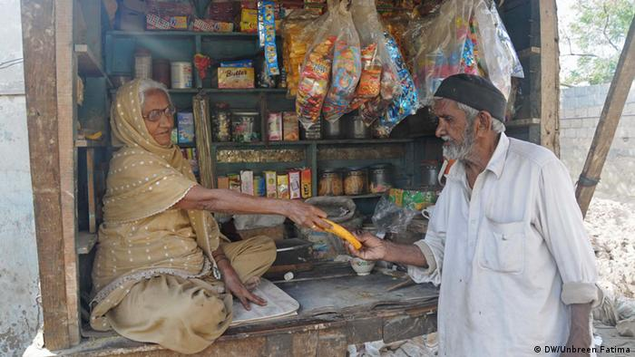 Pakistan Karatschi old woman sells snacks