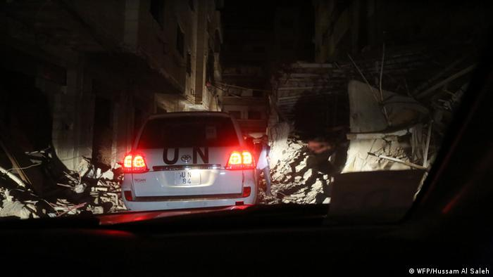 UN convoy makes a night-time delivery of food aid to the besieged town of Daraya, Syria.