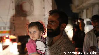 A man holds his young child at the WFP distribution center in Daraya, Syria.