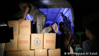 WFP workers off load boxes of food aid from delivery truck in Daraya, Syria