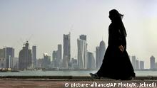 FILE- In this May 14, 2010 file photo, a Qatari woman walks in front of the city skyline in Doha. A lawyer says a Dutch woman who told Qatari police she had been drugged and raped in March has been in government detention ever since on unclear charges. Speaking to The Associated Press, lawyer Brian Lokollo says the 22-year-old woman has appeared three times in court and thinks she may face an adultery charge. (AP Photo/Kamran Jebreili, File) | © picture-alliance/AP Photo/K. Jebreili