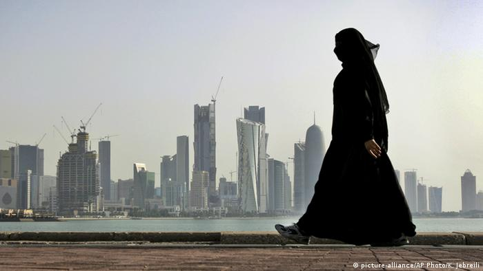 A Qatari woman walks in front of the city skyline in Doha