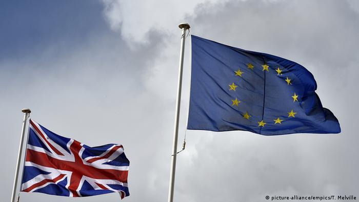 Британский флаг и флаг ЕС на фоне пасмурного неба