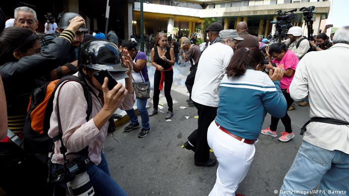 Venezuela Journalisten suchen Schutz vor Tränengas - Demonstration in Caracas