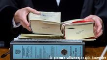 ARCHIV 15.02.2016 - Eine Verhandlungsakte und Gesetzestexte liegen am 15.02.2016 im Landgericht in Frankfurt am Main (Hessen) auf dem Richtertisch. Der Prozess um Steuerbetrug beim Handel mit Luftverschmutzungsrechten gegen frühere Mitarbeiter der Deutschen Bank steht vor dem Abschluss. Foto: Boris Roessler/dpa (zu dpa «Umsatzsteuerbetrug: Urteil gegen frühere Deutschbanker erwartet» vom 11.06.2016) +++(c) dpa - Bildfunk+++ | Verwendung weltweit (c) picture-alliance/dpa/B. Roessler