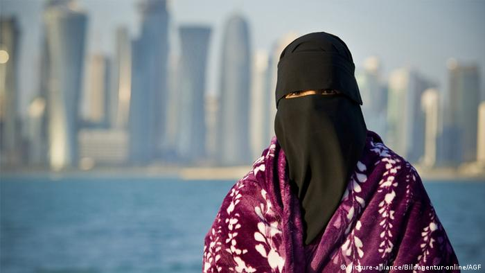 A Saudi woman with the skyline of Qatar's Doha behind her