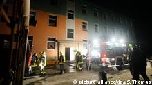 07.09.2016++++++Feuerwehrleute stehen am Morgen des 18.03.2015 vor der Asylunterkunft in Saalfeld (Thüringen) nach einem Kellerbrand. 15 Menschen sind dabei verletzt worden. Insgesamt mussten 94 Personen evakuiert werden. Sie wurden vorübergehend in einer Turnhalle in der Stadt untergebracht. Zur Brandursache liegen derzeit noch keine Informationen vor. (c) picture-alliance/dpa/S. Thomas