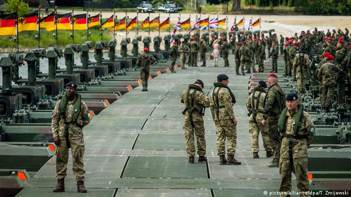 Soldiers stand at the site of the construction of the amphibious bridge across the Vistula river during the NATO Anaconda-16 exercise in Chelmno, Poland