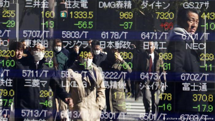 Pedestrians watch Tokyo's stock index outside a securities branch office in the Japanese capital.