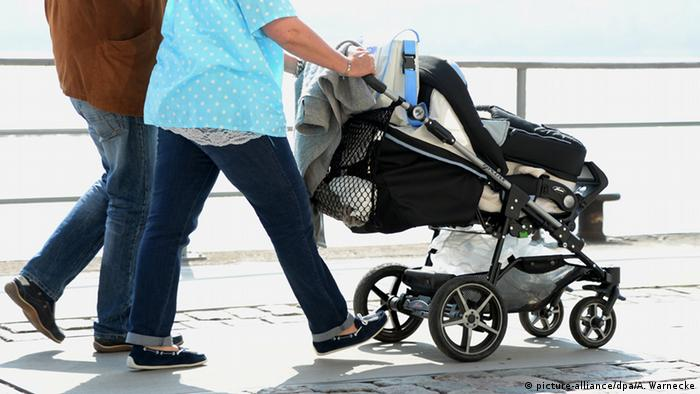 Parents push a baby in a pram