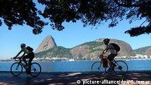 2015 Zwei Radfahrer fahren am 27.05.2015 vor der Kulisse des Zuckerhutes in Rio de Janeiro (Brasilien) auf einem Radweg. Foto: Georg Ismar/dpa (zu dpa «Wird Rio zum Münster Südamerikas?» vom 18.08.2015) +++(c) dpa - Bildfunk+++ (c) picture-alliance/dpa/G. Ismar