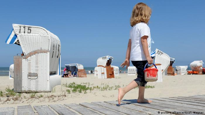 A child on the beach on the island of Spiekeroog in Germany. Photo credit: picture-alliance/dpa/I. Wagner.