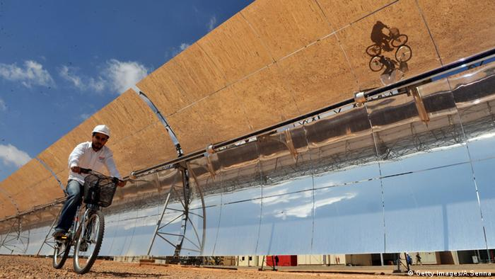 A Moroccan engineer cycles past the solar panels of a solar power station (Getty Images/A.Senna)