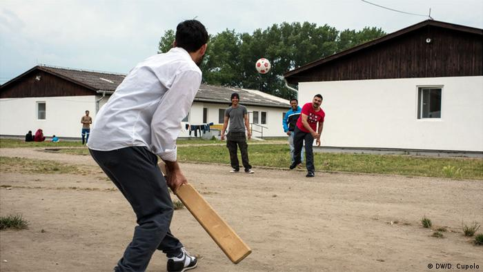 A group of men play cricket with improvised equipment inside Krnjaca Asylum Center