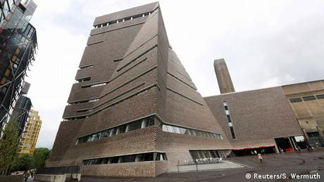 A man stands outside the Switch House during the unveiling of the New Tate Modern in London