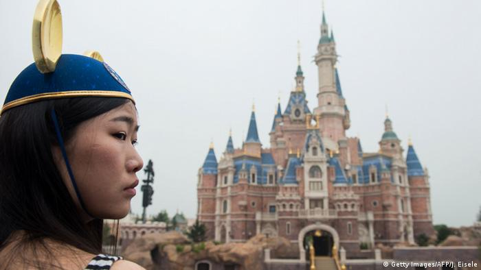 A girl wearing Mickey Mouse ears watches the opening ceremony of the Shanghai Disney Resort in Shanghai