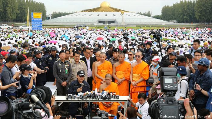 Thai police and monks speak outside of Wat Dhammakaya after a failed police raid