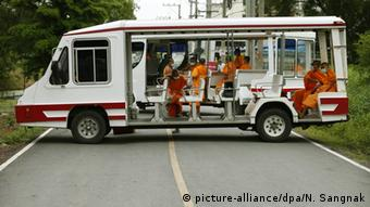 Thai Buddhist monks sit in a car as they block a road leading to the Dhammakaya Temple