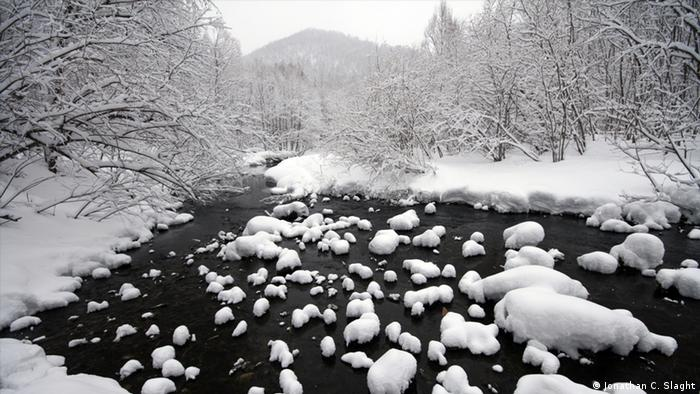 Photo: View of a shallow river on a snowy winter day