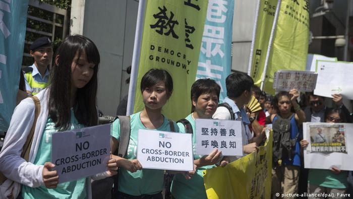 Protesters hold signs that read: No cross-border abduction.