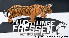 16.06.2016 Flüchtlinge fressen - Not und Spiele steht am 16.06.2016 in Berlin im Rahmen einer Aktion der Aktivisten vom Zentrum für Politische Schönheit auf einem Aufkleber, auf dem ein Tiger-Figur steht. Aktivisiten vom Zentrum für Politische Schönheit haben bei einer Pressekonferenz ihr neues Projekt Das Recht auf Widerstand vorgestellt, in dem Tiger einer Rolle spielen sollen. Foto: Rainer Jensen/dpa (c) picture-alliance/dpa/J. Jensen