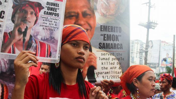 Michelle Campos holds a picture of her father, who was publicly executed for opposing mining in Mindanao, Philippines (Photo: Tulda Productions)