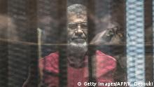 ARCHIV 23.04.2016+++++++++Egypt's ousted Islamist president Mohamed Morsi, wearing a red uniform, stands behind the bars during his trial in Cairo at the police academy in Cairo on April 23, 2016. An Egyptian court postponed its verdict and sentence in the trial of ousted Islamist president Mohamed Morsi, who is charged with spying for Qatar. The head judge of the criminal court said the verdict was postponed to May 7 to continue consultations, in brief remarks aired on television. / (c) Getty Images/AFP/K. Desouki