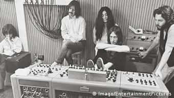 Filmstill Beatles Dokumentarfilm Let It Be im Studio: George Harrison, Ringo Starr, Yoko Ono, John Lennon, Paul McCartney sitzen vor dem Mischpult und hören sich mit ernsten Gesichtern eine Aufnahme an