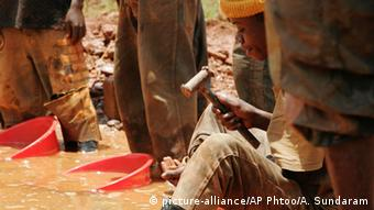 Man sits in muddy water holding a hammer