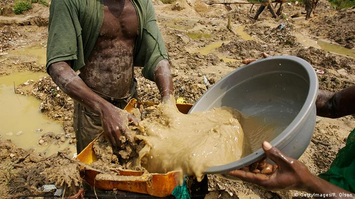 Man washed soil in a bucket in a muddy landscape