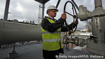 Человек закручивает вентиль на газопроводе