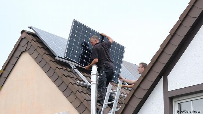 Trabajadores instalando paneles solares en Alemania.