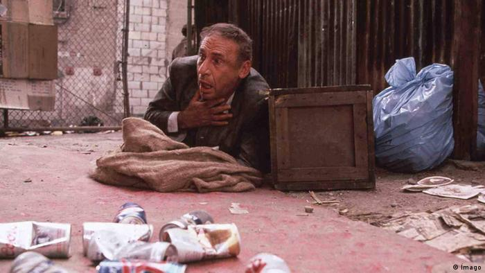 Film still 'Life stinks', a man looking ashast and clutching his throat lies on the ground (Foto: imago)