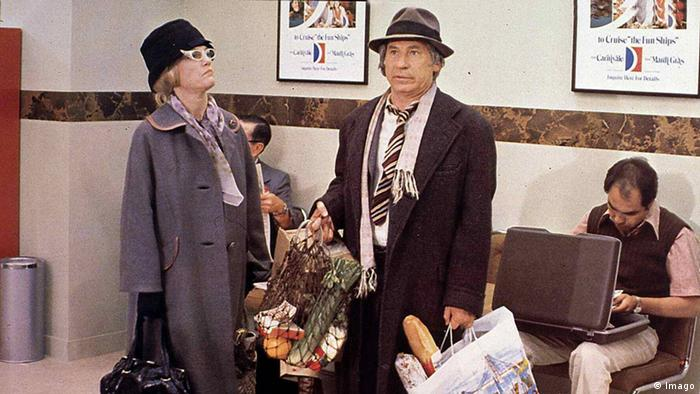 Film still 'High Aanxiety,' two people sittting in what lookjs like a waiting room, a man and awoman holding bags of groceries stand(Foto: imago)