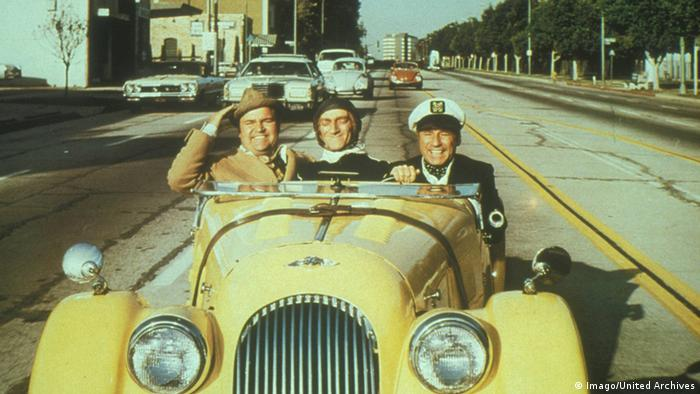 Film still 'Silent Movie', three smiling mendriving in an old fashioned open.top car (Foto: imago/United Archives)